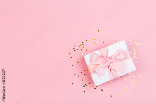 Gift or gift box and stars confetti on a pink table from above. Flat composition for birthday