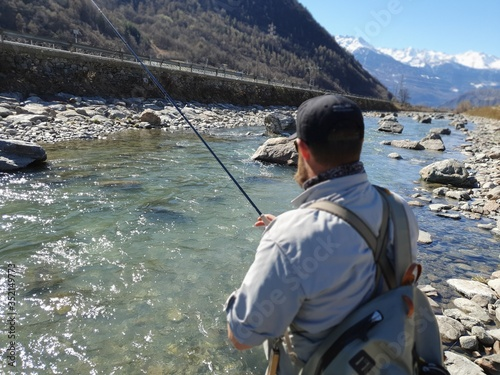 A man Fly Fishing on the Adda River, with picturesque mountains in the backdrop Wallpaper Mural