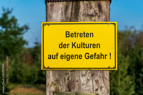 Yellow warning sign with German text Entering the crops at your own risk in front of conifer tree crops on a sunny day in Germany Wallpaper Mural