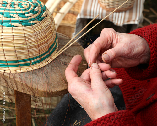 hands with arthrosis of the old lady as she creates a wicker bas Canvas Print