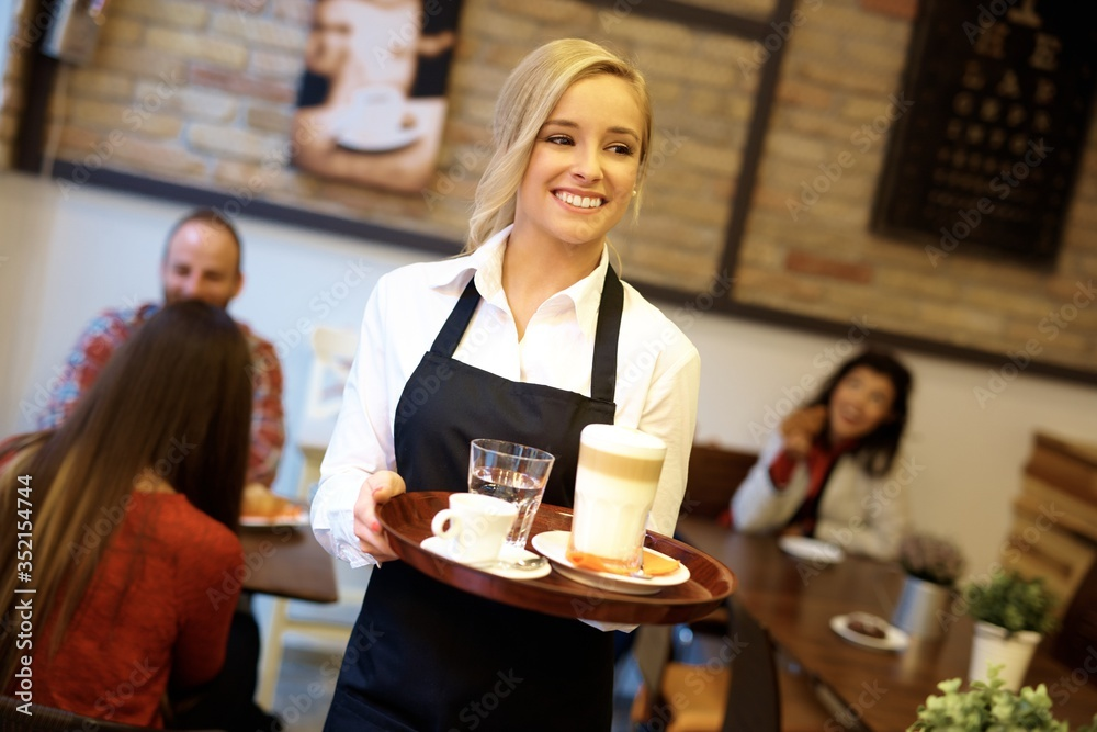 Fototapeta Happy blonde waitress holding tray, working in cafeteria.