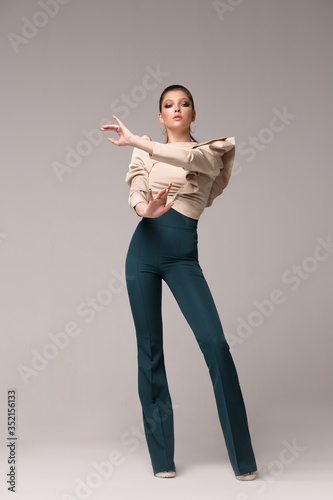 Woman model in stylish fashionable clothes posing in growth in the studio. A beige blouse with lush long sleeves, long green flared pants with a high waist. Hands in front of you.