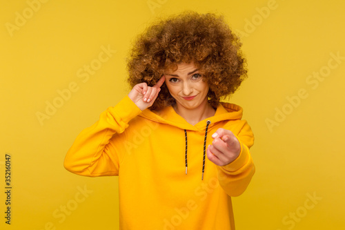Obraz na plátně You are crazy! Portrait of curly-haired woman in urban style hoodie making stupid sign with finger near head and pointing to camera, gesturing bad mind, dumb insane idea