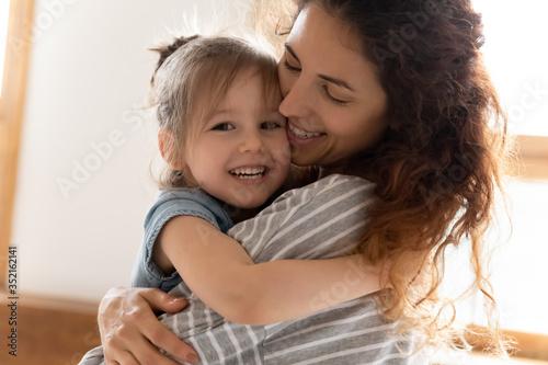 Head shot portrait close up loving mother and adorable little daughter cuddling, Fototapeta