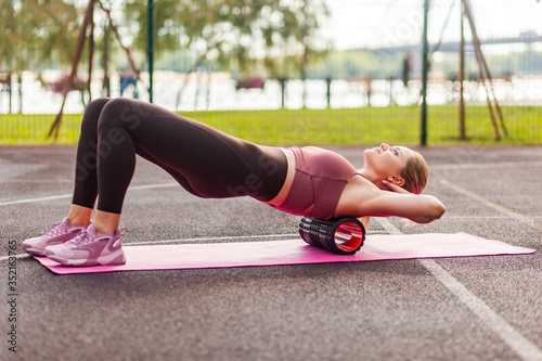 Valokuva Fit blond woman training on mat outdoor summer day, using foam roller massager on her shoulders for relaxation, stretching spine muscles, doing fascia exercise