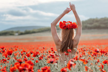 A Blonde Girl With A Bare Back And A Wreath Of Poppies On Her Head Is Sitting In A Poppy Field.