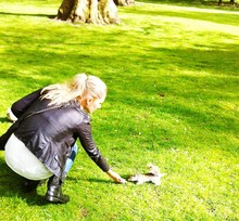 Woman Feeding Squirrel On Gras...