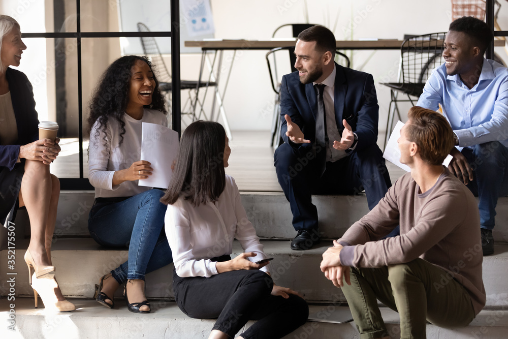 Fototapeta Happy successful business team sitting on stairs in office, having fun at work, diverse coworkers chatting, laughing at colleagues joke, positive employees enjoying break at work together