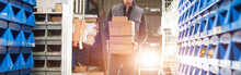 Widescreen Image, Delivery Man In Gray Uniform Carries Boxes In His Hands At The Warehouse. Gold Backlight.