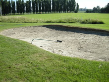 Sand Trap At Golf Course By Trees On Sunny Day