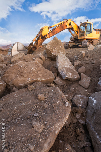 Fotomural Excavator in a quarry extracting stone