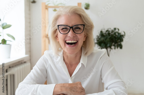 Obraz Headshot portrait of excited mature businesswoman in glasses have fun laugh talking on video call, overjoyed happy middle-aged woman employee smile joke speaking online on WebCam conference - fototapety do salonu