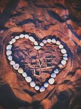 Pebbles Arranged Into Heart Shape On Sand