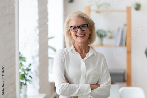 Fototapeta Portrait of smiling senior businesswoman in glasses standing posing in modern office, happy confident middle-aged female employee or CEO look at camera show confidence and success at workplace obraz