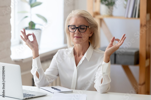 Photo Calm middle-aged businesswoman sit at desk in office relax practice yoga at work