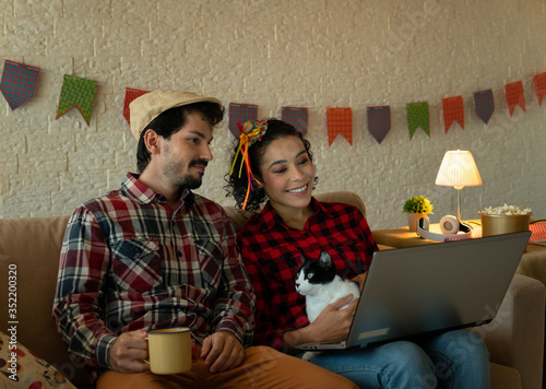 Fototapeta Joyful Young adult brazilian woman with boyfriend watching live stream music or movie on laptop Inside the house in living room. Traditional brazilian june festival, party, celebration concept. obraz