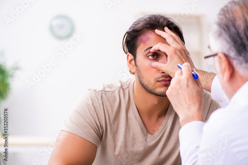 Obraz Young face injured man visiting experienced male doctor traumato - fototapety do salonu