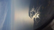 Aerial View Of Sea Against Sky During Sunset Seen Through Airplane Window