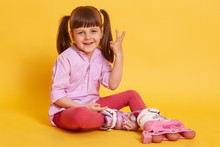 Portrait Of Funny Pleasant Little Kid Making Gesture, Raising Two Fingers, Smiling Sincerely, Having Rest, Sitting On Floor, Wearing Roller Skates, Having Two Ponytails, Being Alone. Games Concept.