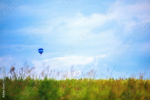 Distant View Of Hot Air Balloon Over Grassy Field Against Sky Fototapet
