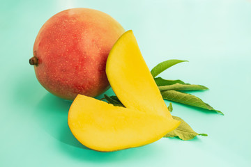 ripe mango and sliced pieces on a green background