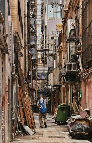 Fotografia Man Walking Along Clattered Back Alley