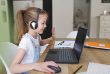 Beautiful Young Girl With Headset Is Sitting In Front Of Her Laptop During Corona Time And Is Having Video Call