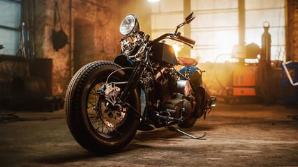 Prilagođeni motocikl Bobber stoji u autentičnoj kreativnoj radionici. Motocikl u vintage stilu pod toplim svjetlom lampe u garaži.