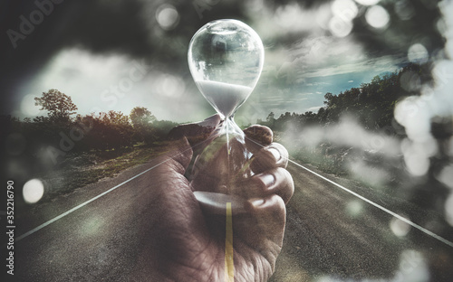 Fotografie, Tablou Double exposure open road and hand holding hourglass