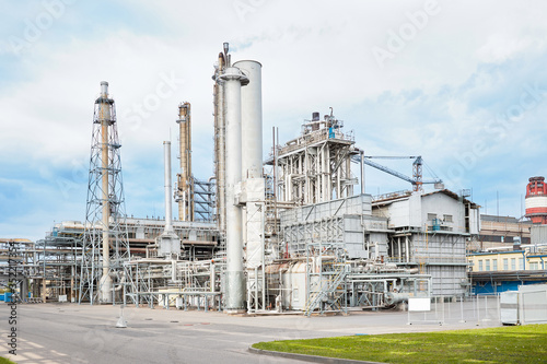 Photo Exterior of modern of petrochemical installation with silver colored stainless reactors and converters furnace chimneys communications under heavy sky background with copyspace and mockup
