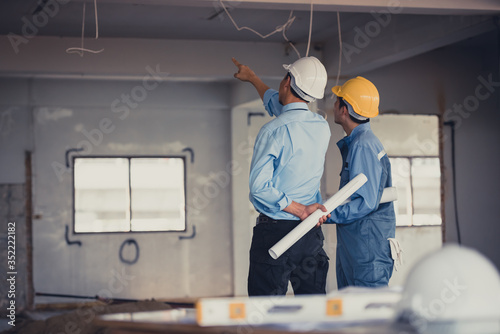Engineer team with hard hat and blueprint talking together at the building construction site Canvas Print