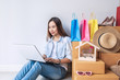 Young asian woman with colorful shopping bag, fashion items and stack of cardboard boxes at home, Website online shopping concept with copy space