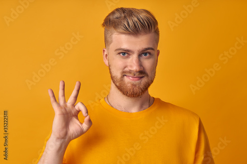 Glad satisfied man with beard shows okay gesture or approval sign, gives positiv Canvas Print
