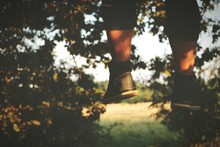Low Section Of Man Legs Hanging Mid-air In Park