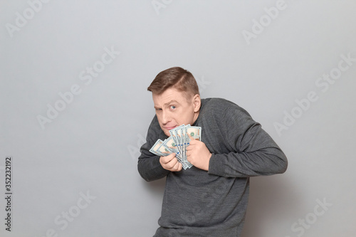 Fototapeta Portrait of funny unhappy greedy man clasping money to his chest