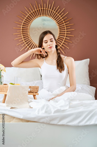 Dreamy and airy-fairy sitting girl on bed in bright morning light Wallpaper Mural