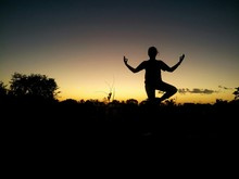 Silhouette Woman Practicing Yoga Against Sky During Sunset
