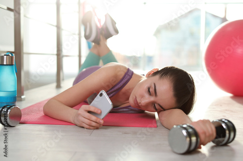 Photo Lazy young woman with dumbbell and smartphone on yoga mat indoors