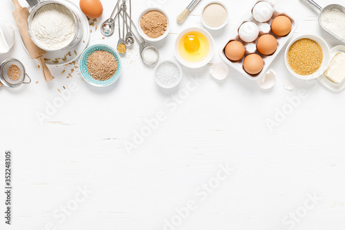 Fototapeta Baking homemade bread on white kitchen worktop with ingredients for cooking, culinary background, copy space, overhead view obraz