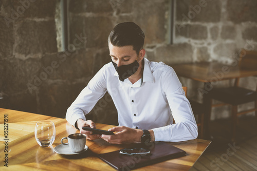 Foto Young fashion Businessman with face mask drinking espresso coffee in the city ca
