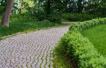 Beautiful Paved Path In The Modern Park Of Tiles And Stone With Green Fences. Without People.