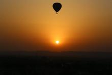 Silhouette Hot Air Balloon Flying Over Landscape Against Orange Sky