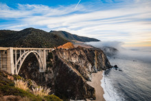 Bixby Bridge Foggy Sunset Landscape In Big Sur Area On The California Coast With Ocean Waters Crashing On The Shore.