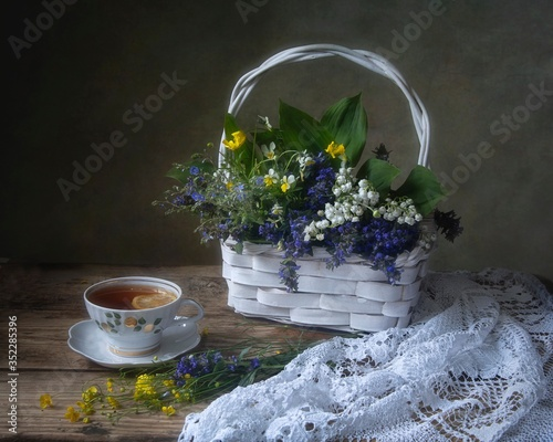 Fototapeta Still life with basket of forest flowers and tea cup  obraz