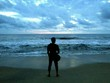 Rear View Of Silhouette Man Standing At Beach Against Cloudy Sky
