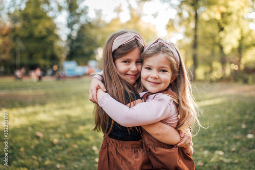 Fotografie, Obraz Outdoor portrait of a two beautiful little sisters in the park.