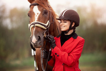 Portrait Jockey woman rider with brown horse, concept advertising equestrian club school
