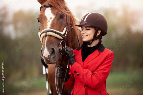 Fototapeta Portrait Jockey woman rider with brown horse, concept advertising equestrian club school obraz