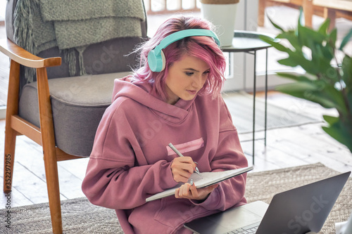 Obraz na płótnie Focused hipster teen girl school college student pink hair wear headphones write notes watching webinar online video conference calling on laptop computer sit on floor working learning online at home