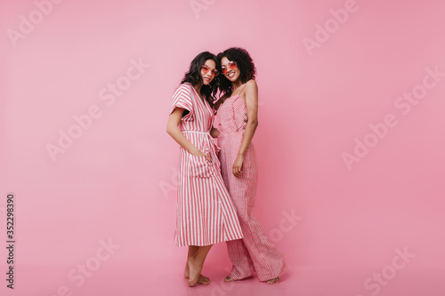Photo Full-length portrait of magnificent ladies in summer clothes smiling on pink background